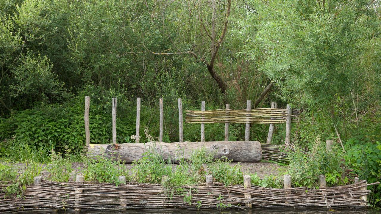 photographie d'une terrasse aménagée au bord de l'eau, un tronc sert de banc et des barrières de saules ont été tressé sur les berges et sur une barrière en bois derrière le banc