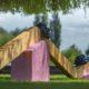 photographie d'une sculpture, posée sur la pelouse. Composée d'une longue poutre en bois aux lignes cassées, soutenues par des support en enduit rose. Quatre serpentins en céramique bleus sont disposés sur la poutre