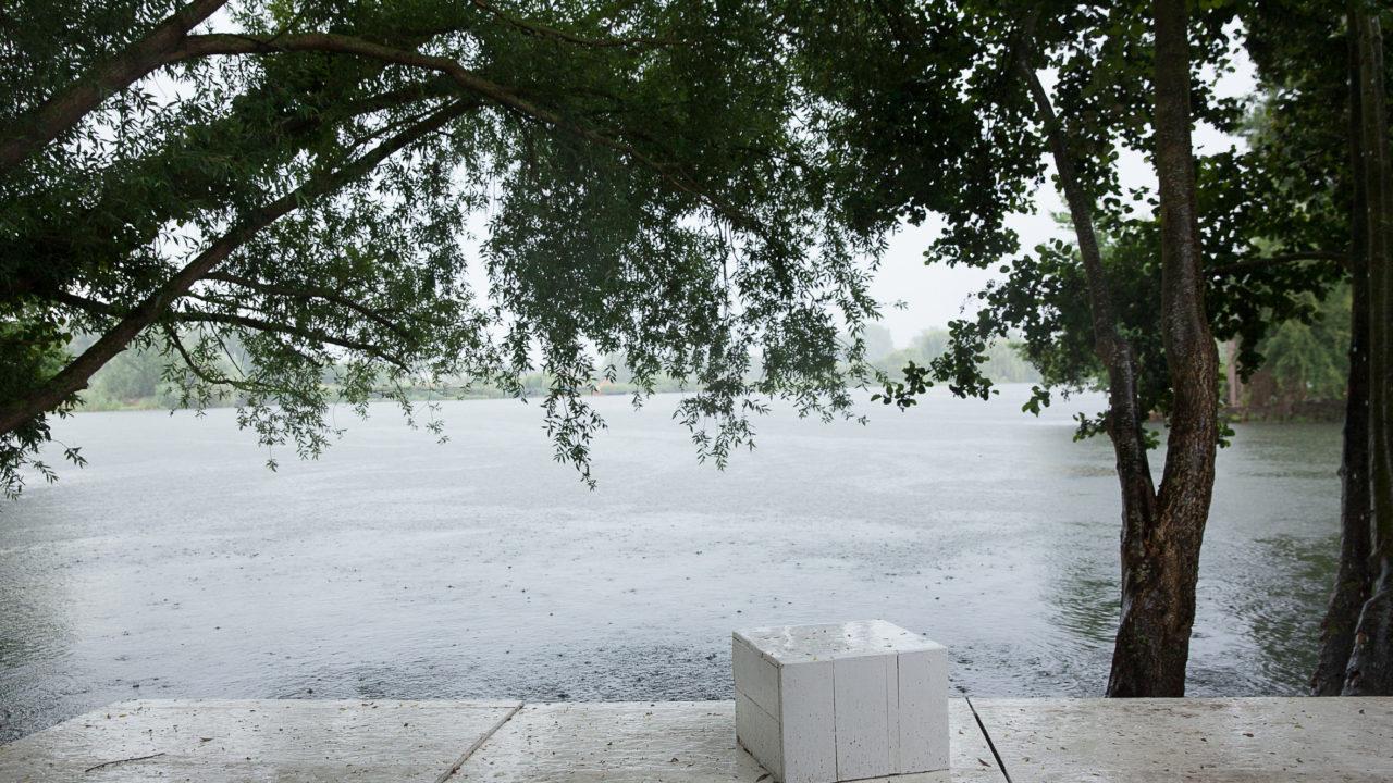 photographie d'une vue sur les Hortillonnages depuis la parcelle de l'oeuvre Syndrome de la page blanche. Un cube blanc est posé sur un parquet blanc, au bord de l'eau.
