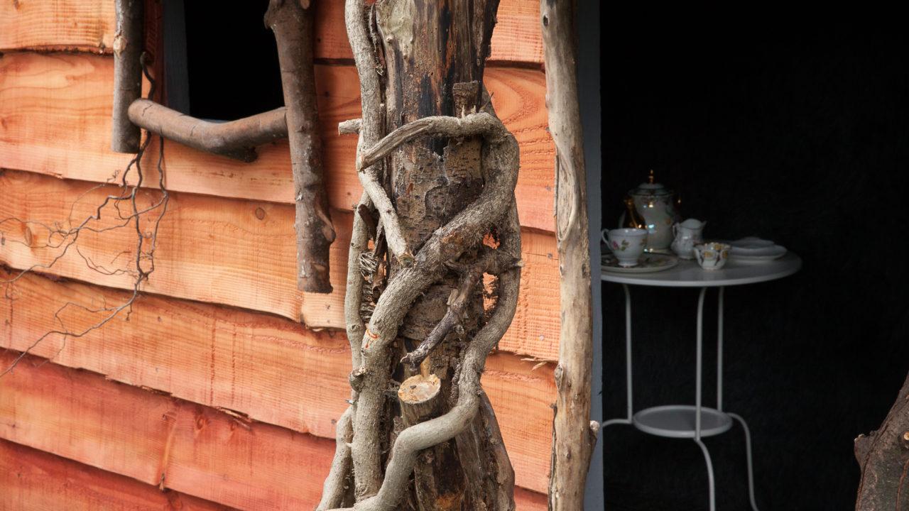 photographie d'une cabane en bois clair, avec à l'intérieur une table blanche avec un service à thé