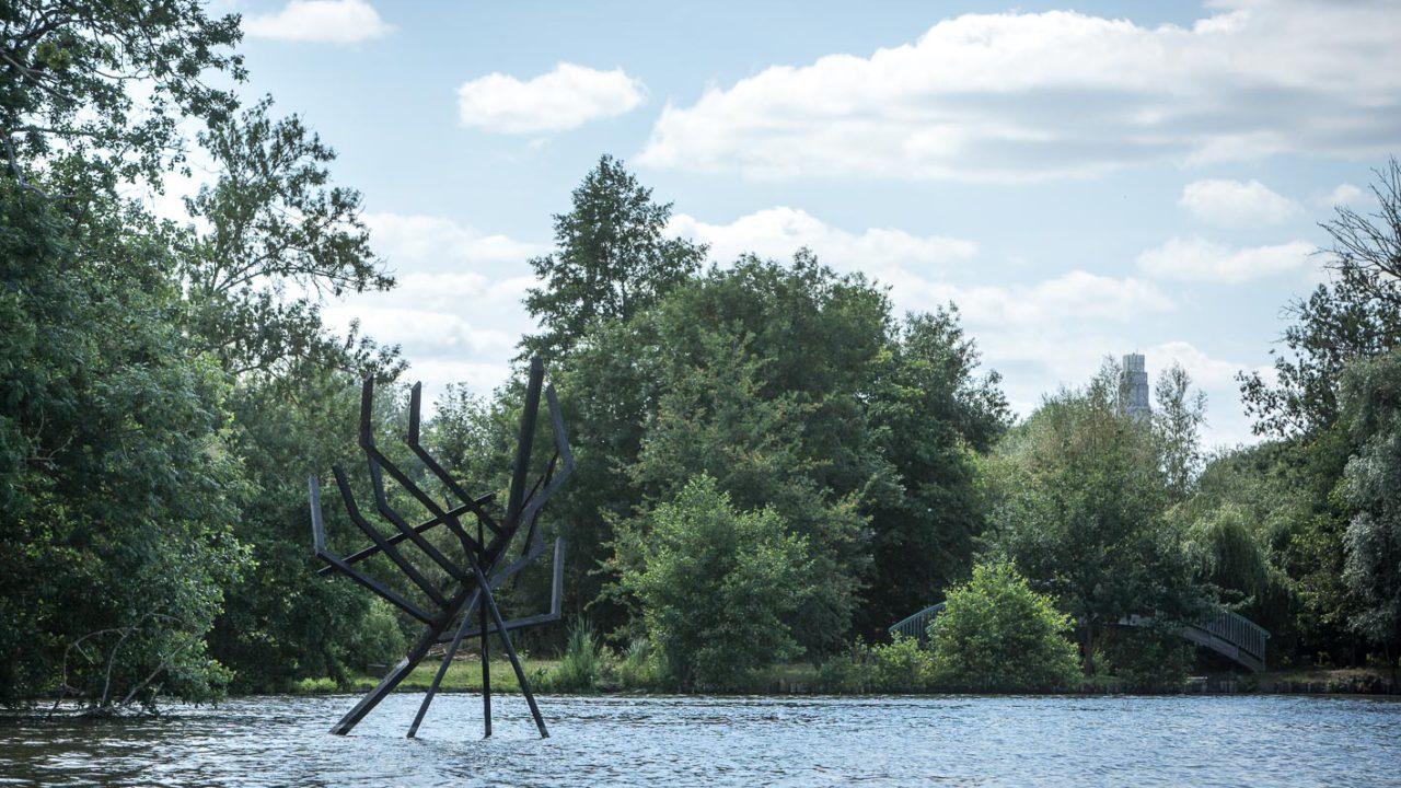 photographie d'une sculpture en bois noir, dans l'eau, ressemblant à une épave de bateau