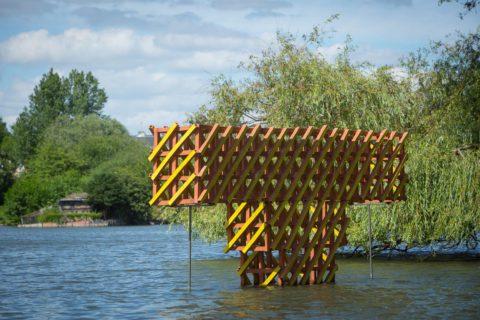 photographie d'une sculpture orange et jaune, dans l'eau, en forme de T, faite en quadrillage