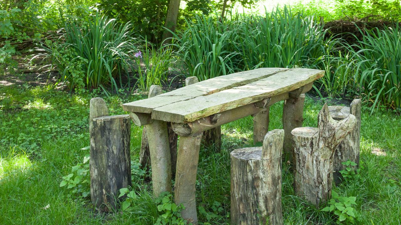 photographie d'une table en bois et de ses 6 assises en bois au milieu d'un jardin verdoyant