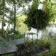 photographie d'un jardin composé d'une parcelle métallique, d'une assise métallique et d'une table métallique. Des boules de plantations sont accrochées en hauteur