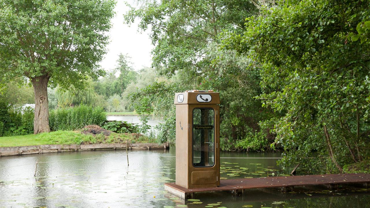 photographie d'une cabine téléphonique anglaise jaune sur un ponton amenant directement sur l'eau