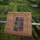 photographie d'un plan puzzle en bois, accroché à un parcelle en hauteur qui donne vue sur des plantations