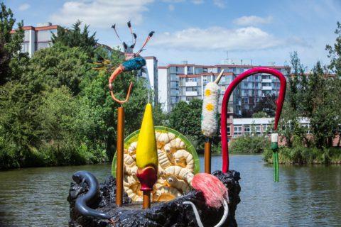 photographie d'une sculpture avec des grands hameçons colorés, posée au milieu de l'eau. Au fond des immeubles d'habitations