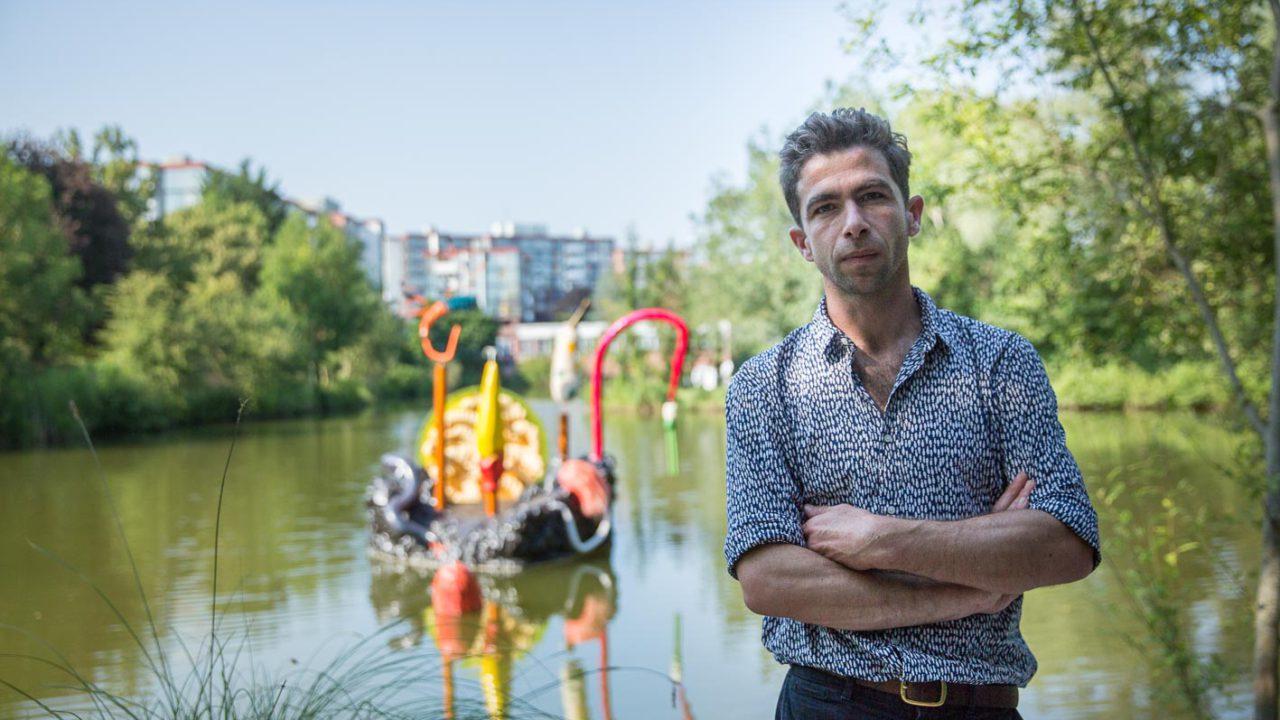 photographie de l'artiste devant son oeuvre, au bord de l'étang de Rivery. Au deuxième plan une sculpture avec des hameçons colorés flotte sur l'eau