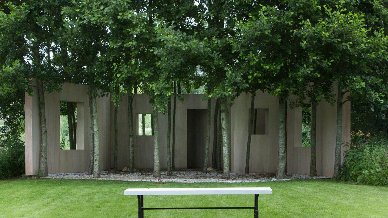 photographie d'un pan de mur en bois, avec des ouvertures comme des fenêtres, devant un espace délimité avec des arbres et un parterre blanc. Au premier plan, un banc est posé sur la pelouse