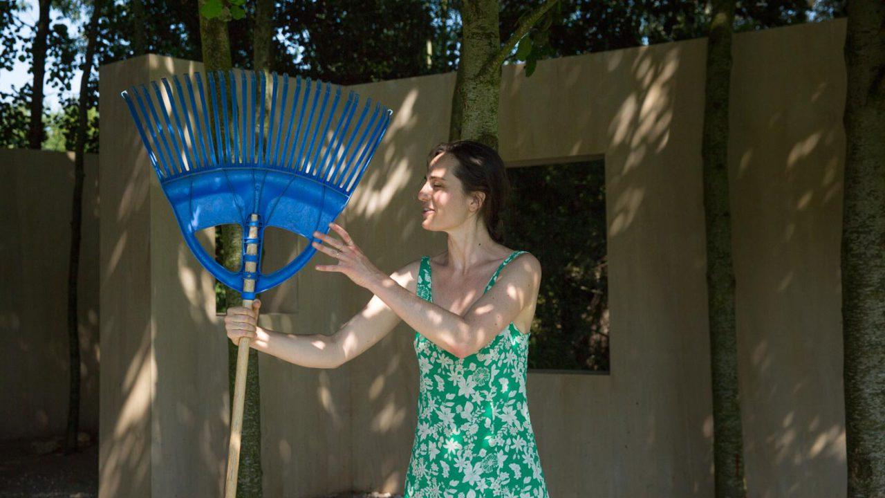 photographie de l'artiste devant son oeuvre, un râteau bleu à la main