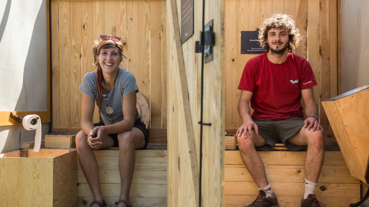 photographie des deux artistes assis dans les toilettes en bois du Jardin du pot commun