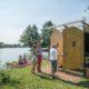 photographie des toilettes en bois sur une parcelle des Hortllionnages, deux visiteurs regardent, un ouvre la porte d'un des toilettes