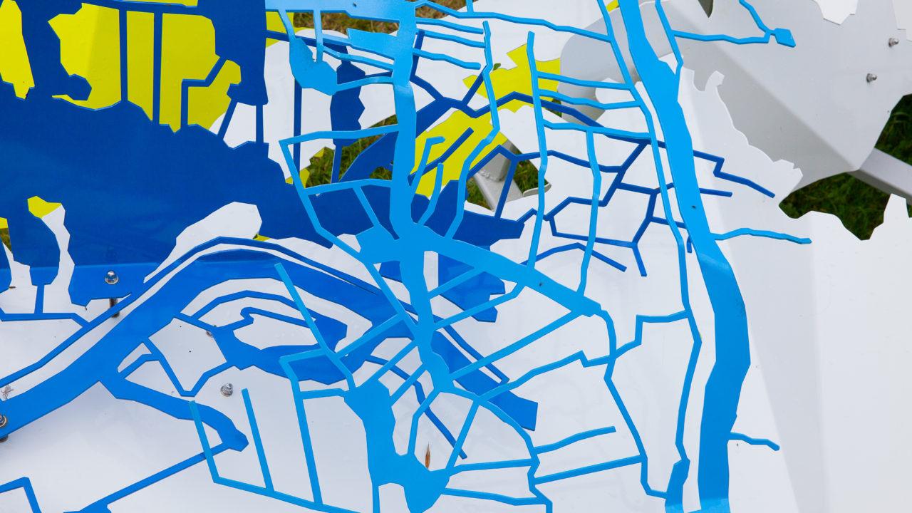 photographie d'une sculpture avec un plan des Hortillonnages plié, en couleurs bleu, blanc et jaune. Détail de l'oeuvre