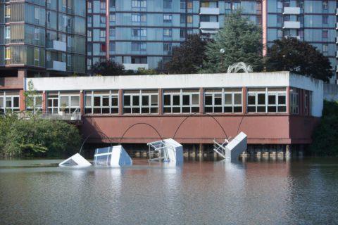 photographie d'une sculpture reliant la toiture de l'immeuble près de l'eau à quatre faux morceaux du bâtiment tombant dans l'eau, créant ainsi une impression de ricochet