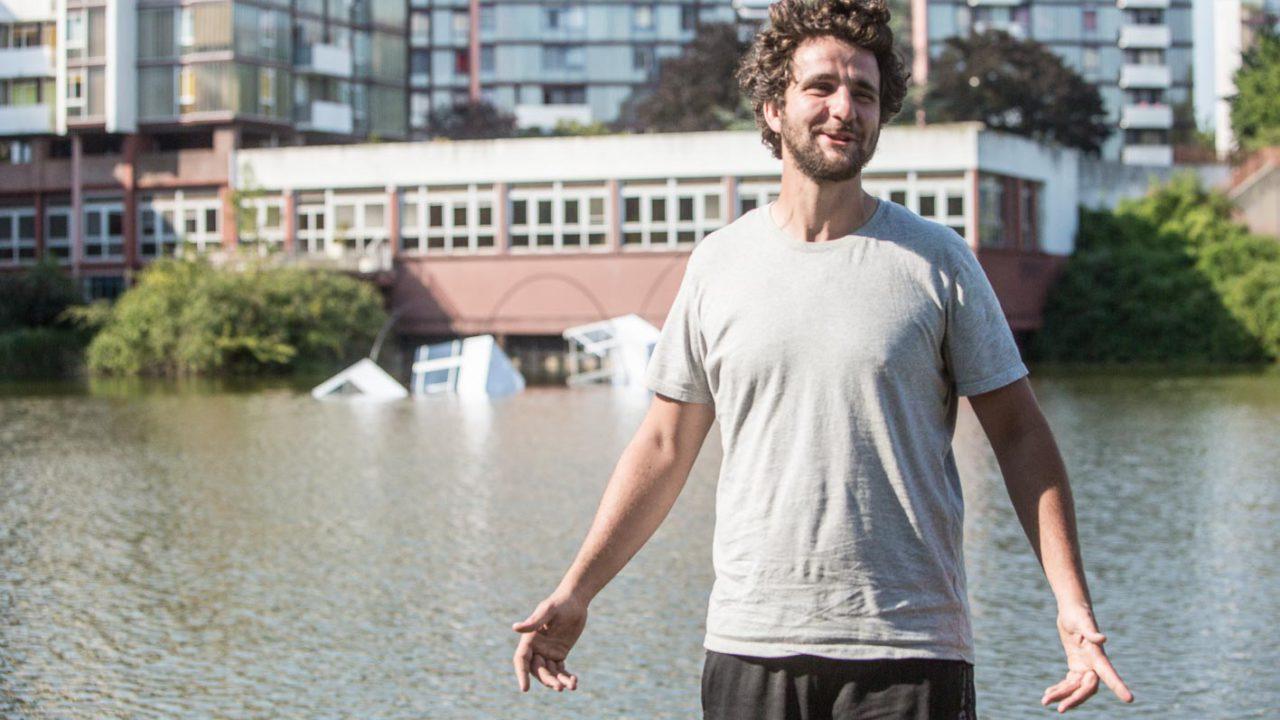 photographie de l'artiste devant son oeuvre au bord de l'étang de Rivery