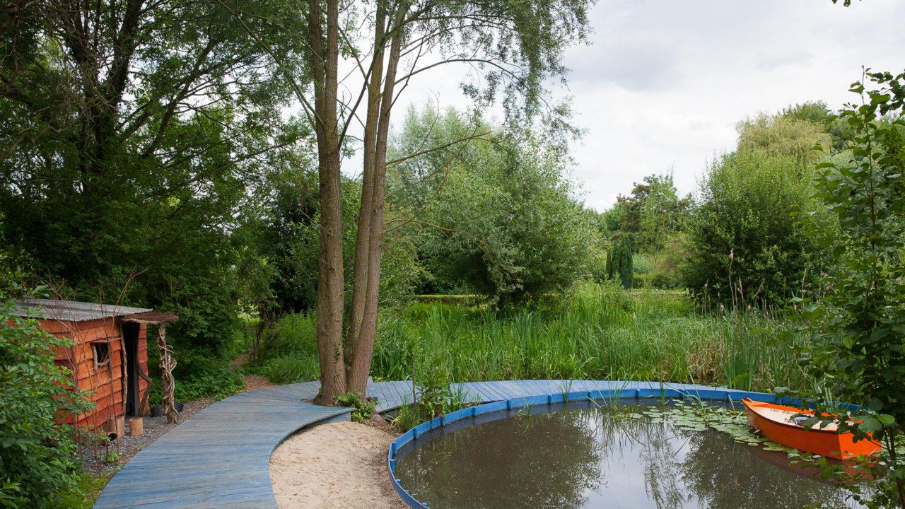 photographie d'un jardin avec un étang circulaire, encerclé d'un parquet bleu en bois, une barque orange est sur l'étang. A gauche, il y a une cabane en bois