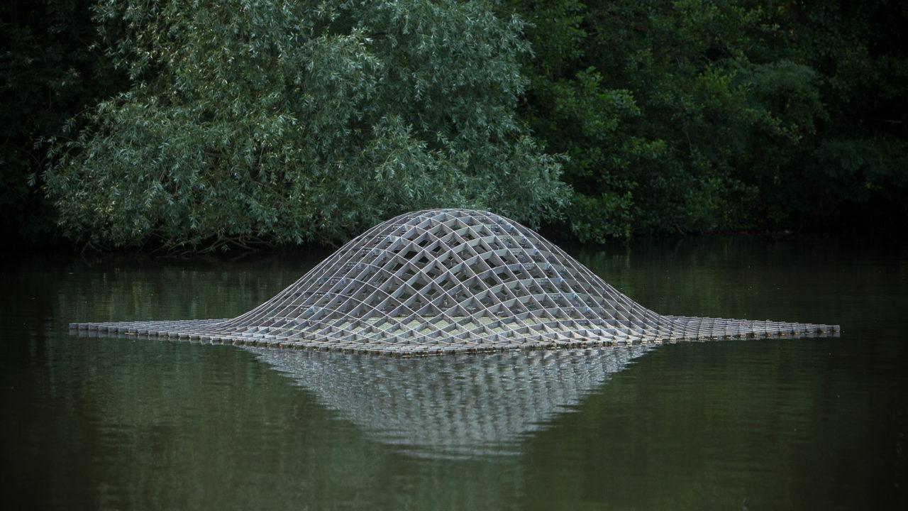 photographie d'une sculpture métallique quadrillée en relief, en forme de mont, flottant sur l'eau