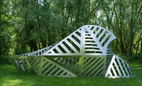 photographie d'une sculpture métallique au milieu d'une parcelle verdoyante. La sculpture reprend la forme du FT17, un petit char chenillé français de la Première Guerre Mondiale