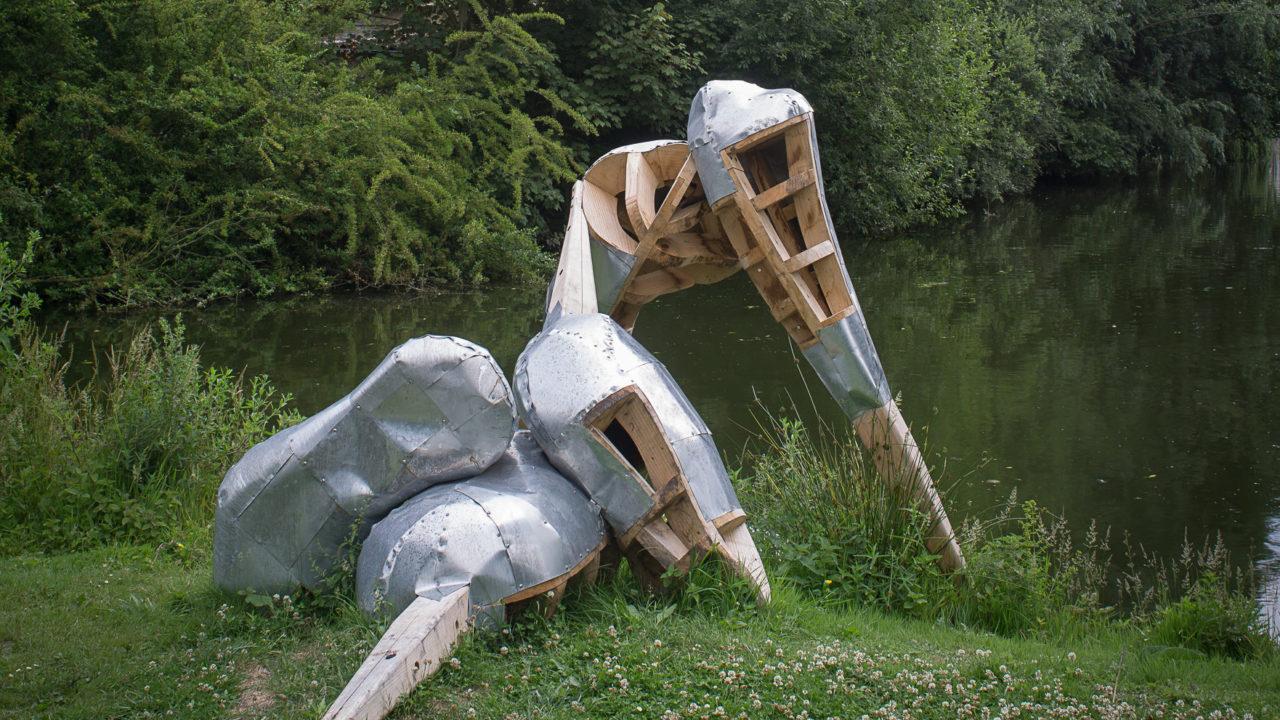 photographie d'une sculpture faite de bois et de métal, au bord de l'eau, sur une parcelle des Hortillonnages