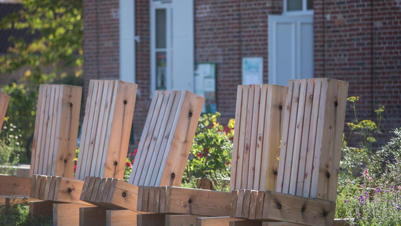 photographie de 5 chaises en bois alignées dans un parterre de fleurs