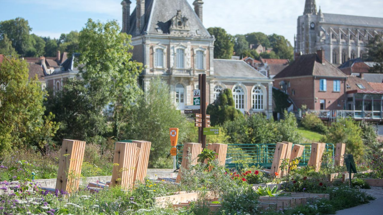 photographie de parterre de fleurs encadrés par des poutres en bois clair, 7 chaises en bois visibles de dos, le long de l'écluse