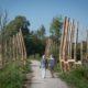 photographie d'un chemin au milieu de deux espaces d'eau, trois structures en bois sont positionnées au bord de l'eau sur ce chemin, deux personnes se promènent