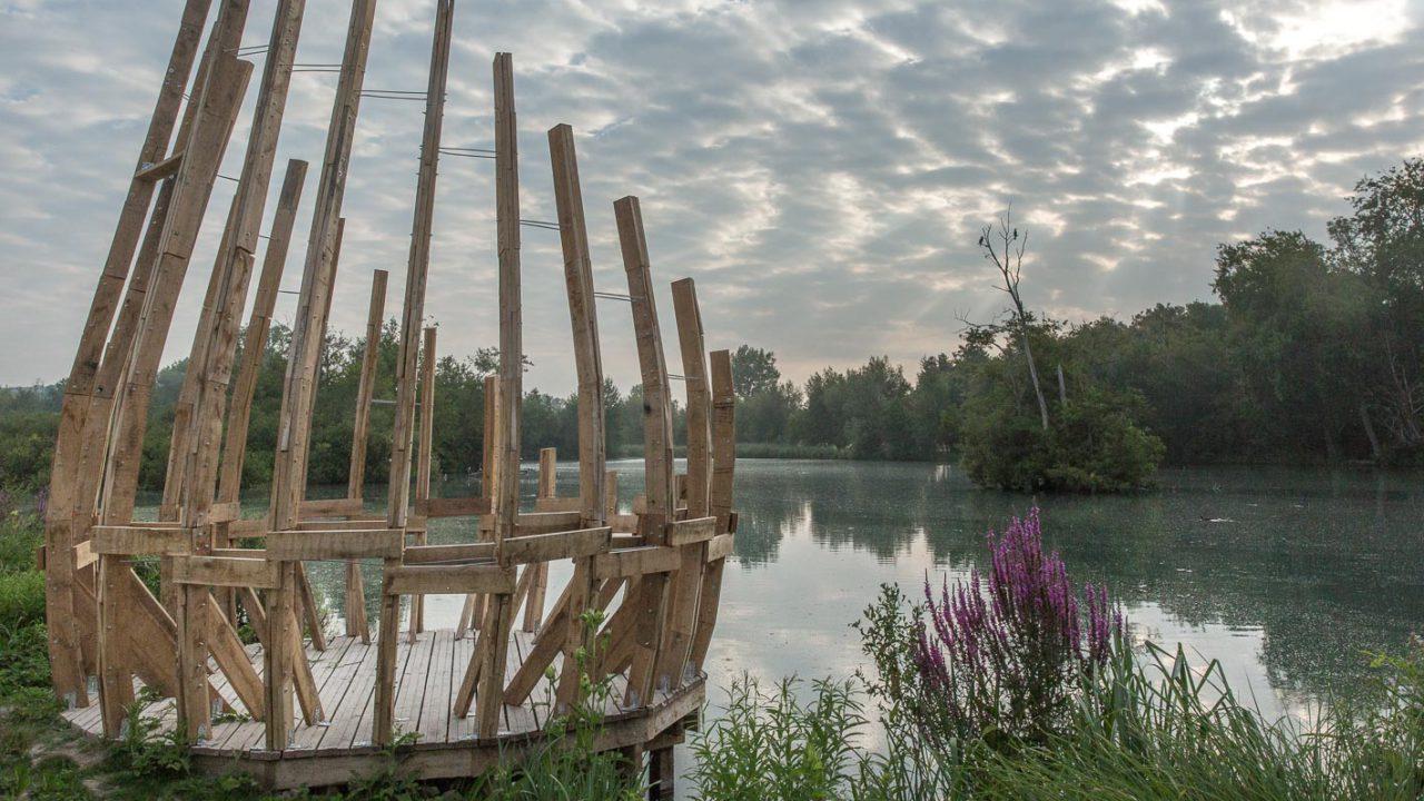 photographie d'une structure en bois en forme de bulbe ouvert, au bord de l'eau