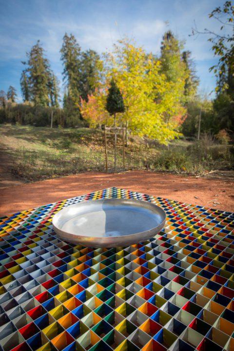 photographie d'un terrain dégagé à la terre bature, au milieu un plan métallique, quadrillé et en différentes couleurs, au milieu de ce plan, une coupelle métallique