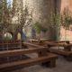 photographie d'un grande terrasse dans les douves du mémorial de Péronne, quatres tables avec des bancs où poussent au milieu des arbres