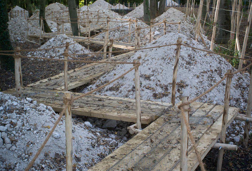 photographie d'un jardin avec une longue passerelle en bois qui serpente entre des tas de cailloux blancs